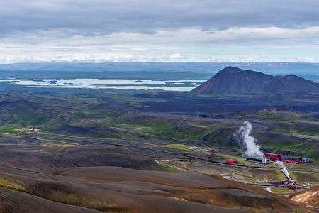 Landscape of Krafla area in northern Iceland with Kroflustod geothermal power plant at right and Myvarn lake at background, Nordurland eystra region. Stok Fotoğraf