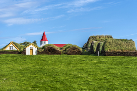 Traditional Icelandic farm Glaumbaer consisting of turf houses in Northern Iceland, as seen from the South door, the top of the wooden church is behind.