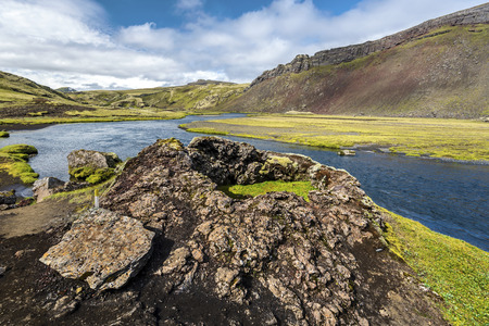 Small volcano crater in Canyon floor of Eldgja in the west of Vatnajokull National park in southern highlands of Iceland. Flow of Nordari-Ofaera river and Canyon wall are at background