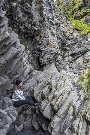 Teenager girl is sitting at Basalt cliffs in the bottom of Reynisfjall mountain. Reynisfjara beach in Southern Iceland. Фото со стока