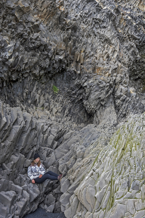 Teenager girl is sitting comfortably at Basalt cliffs in the bottom of Reynisfjall mountain. Reynisfjara beach in Southern Iceland.