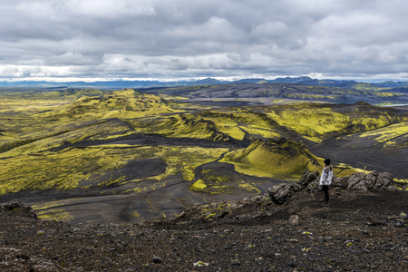 Teenager girl staying in volcano slope facing Southwestern part of Lakagigar volcanic crack in South of Iceland.