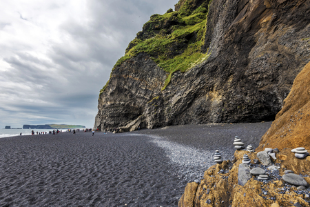 View at Reynisfjara  black sand beach in Southern Iceland. Reynisfjall mountain wall and Gardar basalt columns are at right.