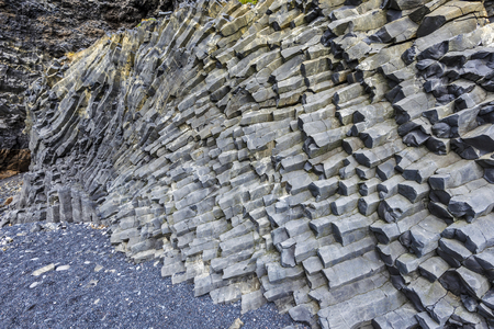 Hexagonal basalt cliffs of the bottom of Reynisfjall mountain in Southern Iceland. Фото со стока
