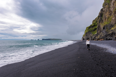 Teenager girl walking along the Reynisfjara black sand beach in Southern Iceland. Reynisfjall mountain and Gardar basalt columns are at right background.