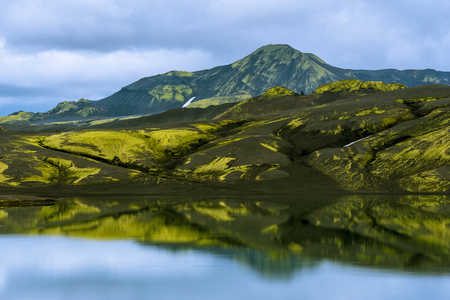Lava formations of Lakagigar volcanic crack area covered with yellow-green Icelandic moss reflecting in the water of Lambavatn lake, Southern highlands of Iceland.