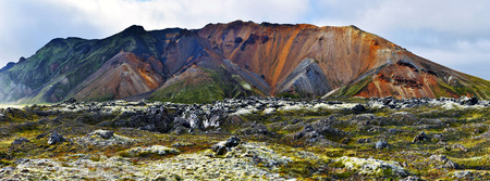 Lava field and mountain landscape panorama of Landmannalaugar in midnight light. Highlands of Iceland, Fridland ad Fjallabaki Natural park in July. Фото со стока