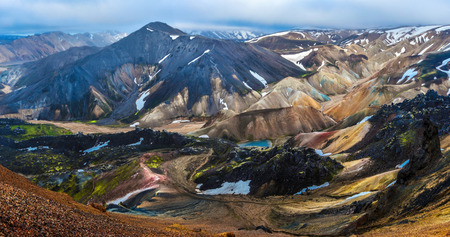 Mountain landscape panorama of Landmannalaugar in midnight light seen from Brennisteinsalda volcano mountain in Highlands of Iceland. Fridland ad Fjallabaki Natural park in July. Фото со стока