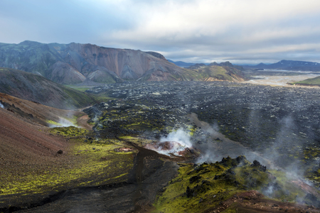Active fumaroles and solfataras in the slope of Brennisteinsalda Volcano mountain in Landmannalaugar region of Iceland Highlands. The lava field and the landscape of Fjallabak Natural park at background.