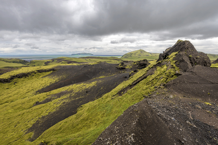 Landscape with sandstone formations covered with green moss, along Kerlingardalur Road, as viewed in south direction, Southern Iceland.