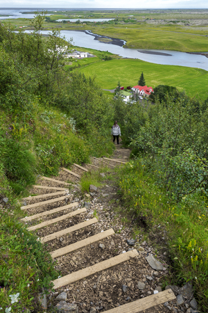 Steps leading down to Kirkjubaejarklaustur village through green vegetation. Skaftarhreppur municipality of Southern Iceland. Фото со стока