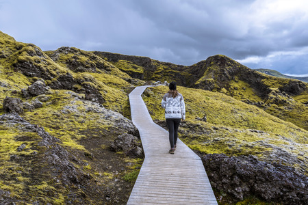 Girl teenager is following wooden foot pass to the crater Tjarnargigur in Lakagigar volcanic fissure area in Southern highlands of Iceland. 写真素材 - 125486536