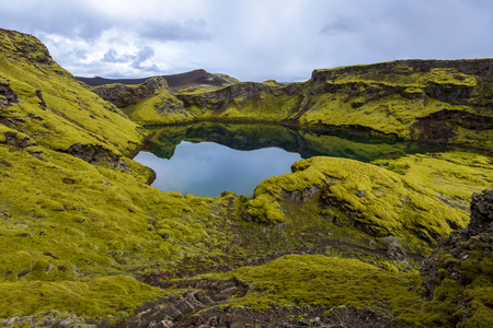 The crater Tjarnargigur filled with water is one of the most impressive craters of Lakagigar volcanic fissure area in Southern Highlands of Iceland. Pond Crater.