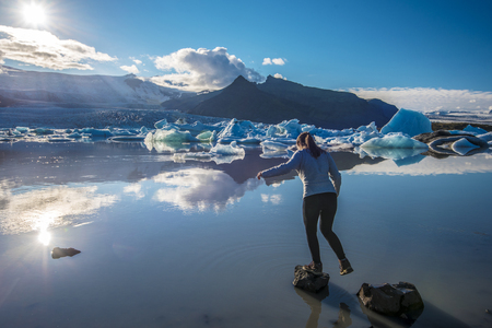 Teenager girl jumping over rocks in the border of Fjallsarlon Glacier Lake facing to the sun. Southern Iceland, Vatnajokull National Park. 写真素材 - 125486198
