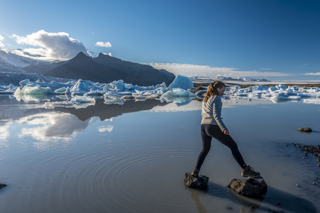 Teenager girl jumping over rocks in the border of Fjallsarlon Glacier Lake. Southern Iceland, Vatnajokull National Park. 写真素材 - 125486201