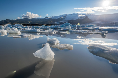 Small ice-bergs reflecting in the water of Fjallsarlon glacier lake facing to the sun. Southern Iceland,  Vatnajokull national park. 写真素材 - 125486202
