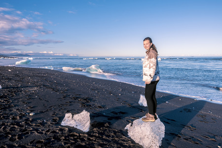 Teenage girl is staying in the small icebergs in the Atlantic Ocean border, close to Jokulsarlon Glacier Lagoon in Southeastern Iceland. 写真素材 - 125486206