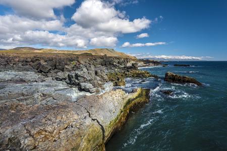 Rocky coastline seen from Fauskasandur beach via Styrmisnes point in Eastern Iceland.