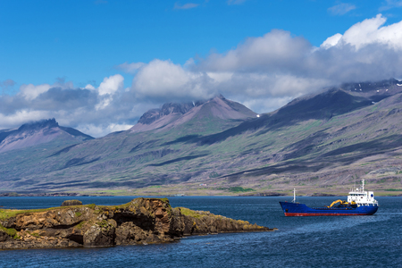 Industrial vessel moving to the Djupivogur town through Berufjordur Fjord in Eastern Iceland. Mountain landscape of the northern coastline of the fjord is at background.