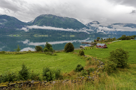 Landscape of Lustrafjorden in Hoyheimsvik area in Norway. Grassland and lonely house are in the border of the Fjord. 写真素材 - 125486129