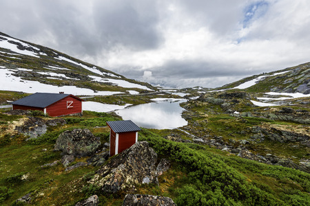 Red wooden hut and toilet are in the border of Galgebergstjornane lake in Norway. The slope of Galgeberg hill and the Norwegian country road 55 are at left.