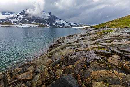Border of Plesteinvatnet lake as viewed in the direction of the dam and steindalsnosi spur at background, covered with heavy clouds. Sogn og Fjordane, Norway. 写真素材 - 125486133