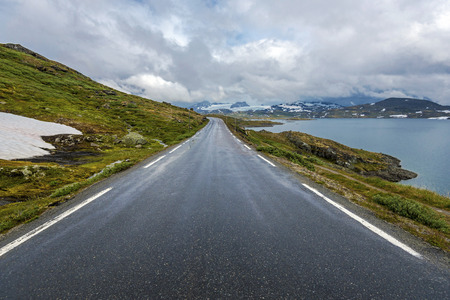 Touristic road 55 seen in Oppland direction, Plesteinvatnet lake is at right. Sogn og Fjordane, Norway. 写真素材 - 125486134