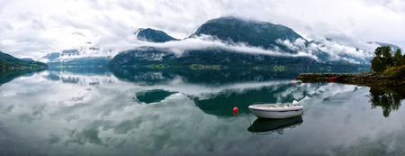 Panoramic view of Lustrafjorden covered with mist, mountains and foggy pattern is reflecting in the water, white boat and lonely hut in the border of the fjord are at right. Hoyheimsvik, Norway.