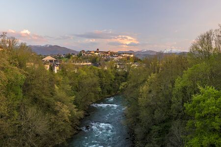 Oloron river and Oloron-Sainte-Marie city in sunset light. Mountains of Atlantic Pyrenees are at background. Bearn, France.