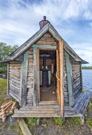Swedish wooden sauna with open door, the woodstove is seen in the interior, the water of Gaxsjon lake is at background. Jamtland county in Northern Sweden.