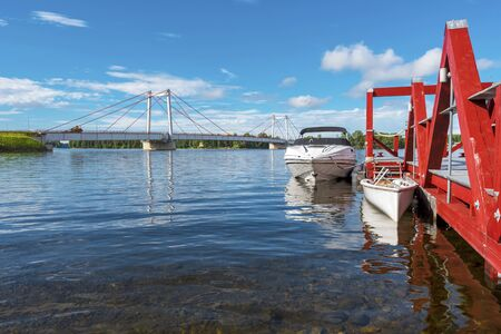 Jetty and motor boats in the border of Stroms vattudal, an extensive water system in Swedish Jamtland. The Stromsund bridge is at left background. 写真素材