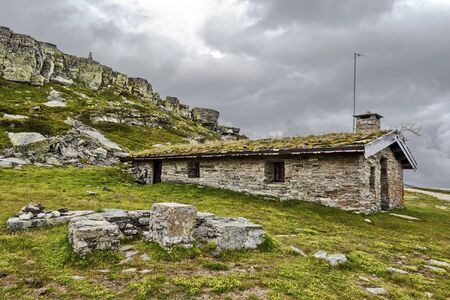 Ancient house of mine workers in Oppland highlands, Norway. Rocky Slope of Gluggen Hill is at background.
