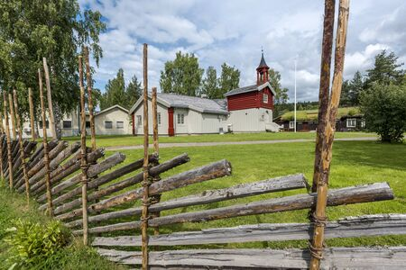 Typical Norwegian Koppang with wooden palisade at foreground. Hedmark county of Norway. Stock Photo