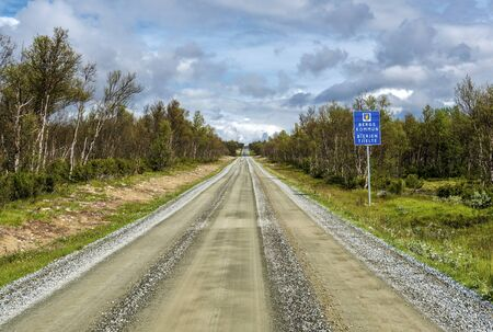 The ground road in northern Sweden crossing tundra forest in Berg municipality of Jamtland county. The wild area perfect for a road trip.
