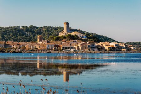 Historical center of Gruissan town with Barberousse Tower in top seen from the opposite side of the pond. Occitanie, France.