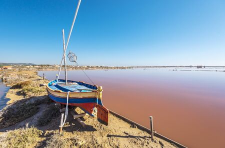 Saline island of Saint Martin de Gruissans, the old wooden ship at left and the reddish colored saturated with salt water at right.  Occitanie, France.