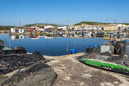 Fishers village in the border of Laguna Ayroll, Narbone region of French Occitania. Small boats, fishing webs and other articles are at foreground.