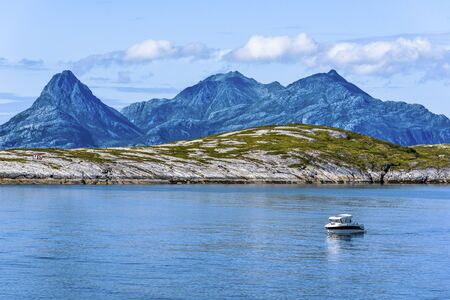 Rocks of Landegode island as seen from Hjartoya Island in Bodo Municipality, Nordland county of Norway. Water of Norwegian Sea and small boat are at foreground. Stock fotó
