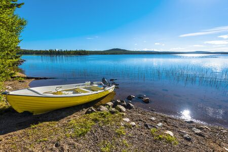 The motor boat in the border of Siebdniesjavrrie lake Swedish Lapland. The sun is reflecting in the water. Vasterbotten county, Norrland, Sweden.