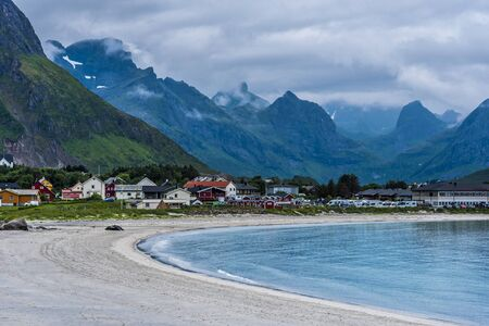 Rambergstranda beach in Lofoten  archipelago, Ramberg village and mountains covered with clouds are at background. Nordland, Northern Norway.