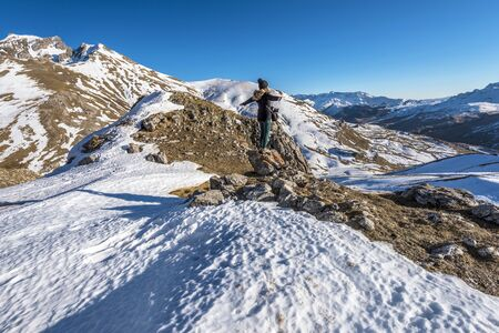 Girl hiker is staying in the stone facing the Tena Valley in the Pyrenees in early winter time. Portalet mountain pass, Aragon, Huesca. 写真素材