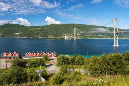 The Tjeldsund Bridge through Tjeldsundet strait as seen in the direction of Hinnoya Island in Norway. Green plants, flowers and trees on the mainland are at foreground.
