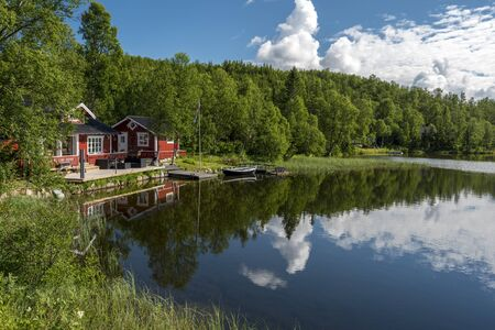 Typical Norvegian house in the border of the lake Lille Trollvatnet. Nordland, Norway. Stock Photo