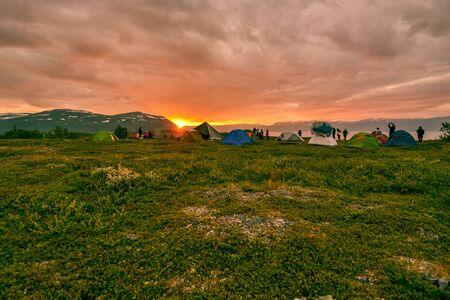 Abisko, Sweden - August 6, 2017 Sunset in National Park Abisko in Northern Sweden. Hikers installing tents face to the grand landscape of Tornetrask lake and mountains of Vadvetjakka national park.