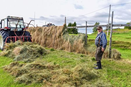 Hetta, Finland - August 4, 2017 Farmer and hayrack, traditional haymaking nordic style in Finnish Lapland.
