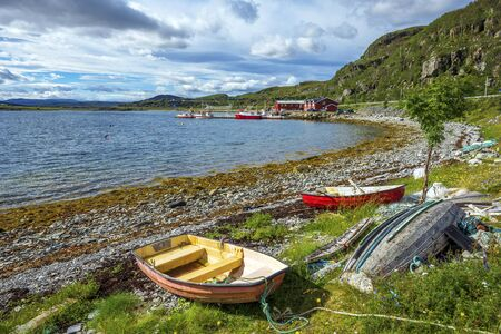 The view at Ytrebukta bay with small boats and fishermen along the coastline of Porsangerfjorden in Norwegian Finnmark, close to the roar via the North Cape. Banco de Imagens