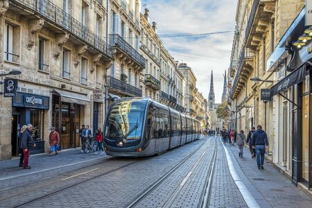 Vital Carles street view in the center of Bordeaux city. The Tramway is in approach, Saint Andre Cathedral is at background.