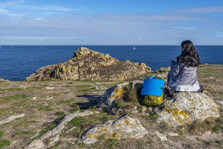 Hoedic, France -November 2, 2018 Woman tourist sitting in the rock acing to the Ocean, Cape Vieux Chateaux, Brittany, France