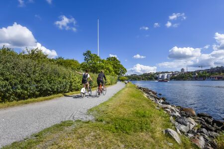 Stockholm, Sweden - August 18, 2017 Cyclist on the water face promenade in Djurgarden island in Center of Stockholm. Waters of Saltsjon bay is at right. 報道画像