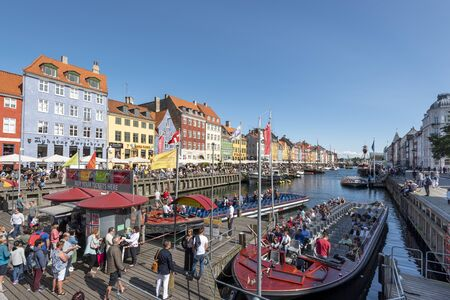 Copenhagen, Denmark - August 23, 2017 Panoramic view at Nyhavn Canal in Copenhagen city. Colorful facades, old ships, touristic boats and crowd of tourists make Nyhavn the most lively place in the capital.